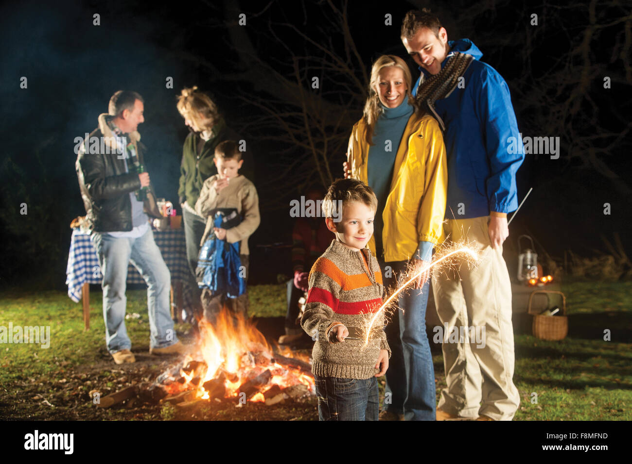Family in garden enjoying a bonfire and playing with sparklers Stock Photo