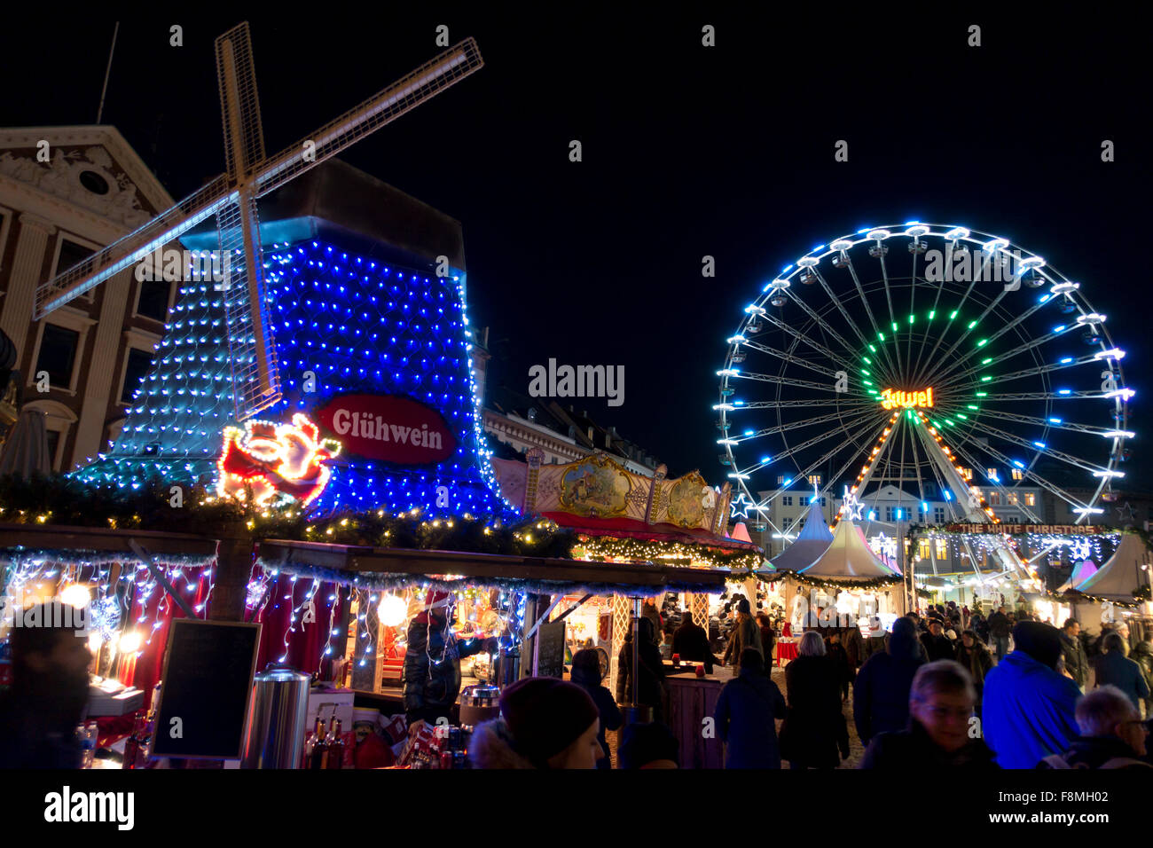 Illuminated, colourful windmill and ferris wheel at the new Christmas market on Nytorv at Strøget in Copenhagen, - Stock Image