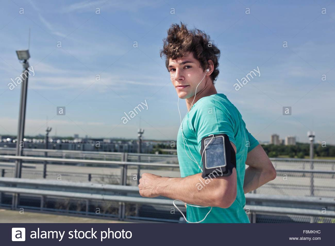Young male runner wearing earphones looking over his shoulder whilst running - Stock Image