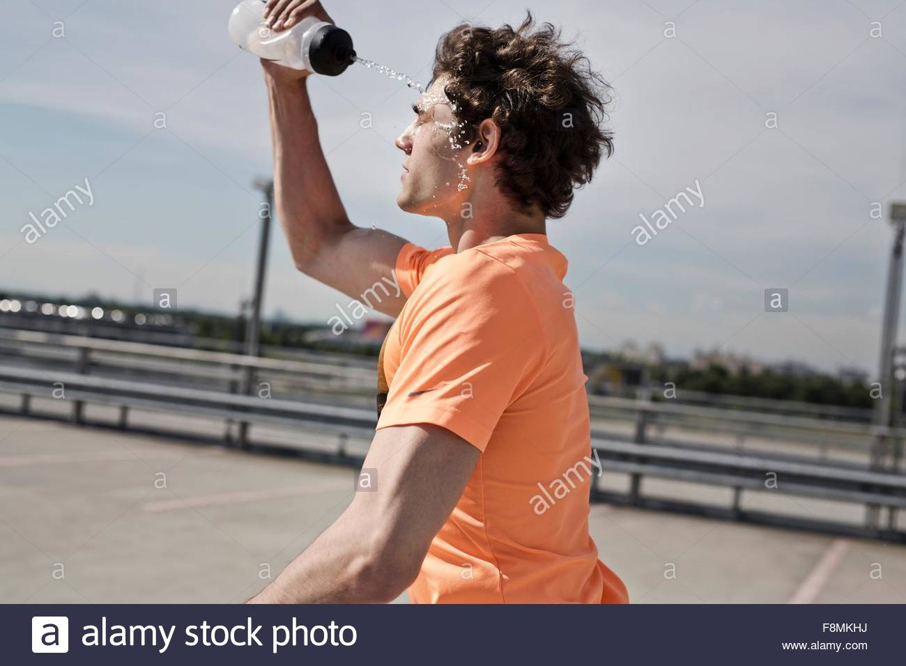 Young male runner pouring water on his face whilst running in city - Stock Image