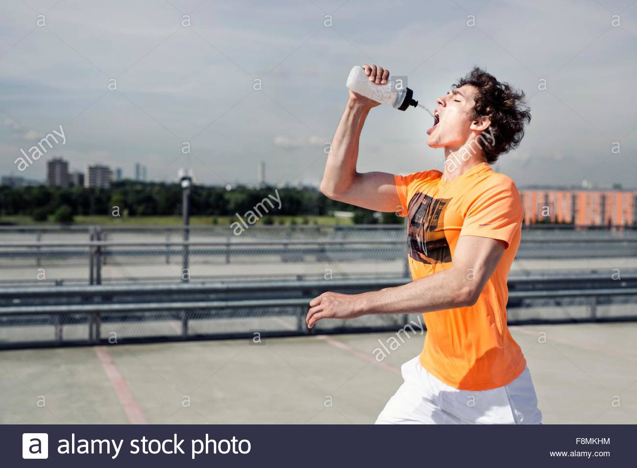 Young male runner drinking water whilst city running - Stock Image