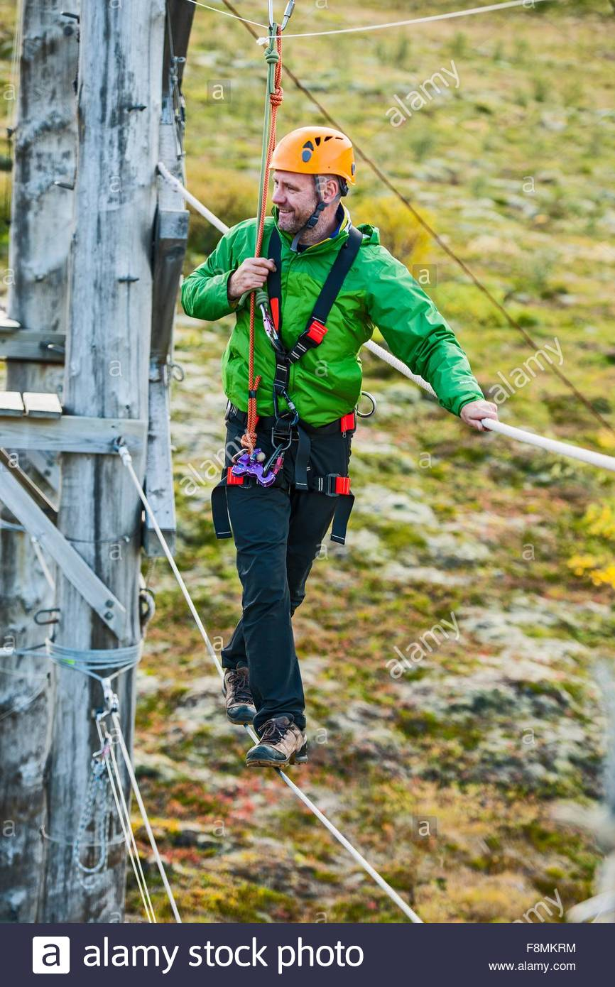Man balancing at high rope access course, Iceland - Stock Image