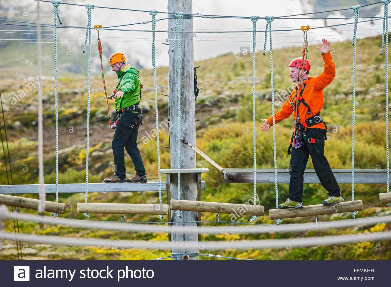 Men balancing at high rope access course, Iceland - Stock Image