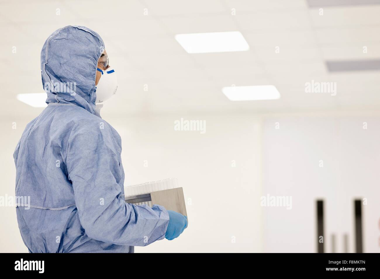 Scientist carrying tray of test tubes in laboratory - Stock Image