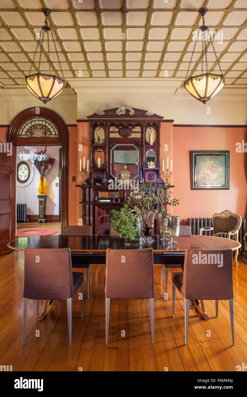 The home of designer Erica Pols. The dining room. Table and chairs, and a large dresser with overmantle. A checked - Stock Image