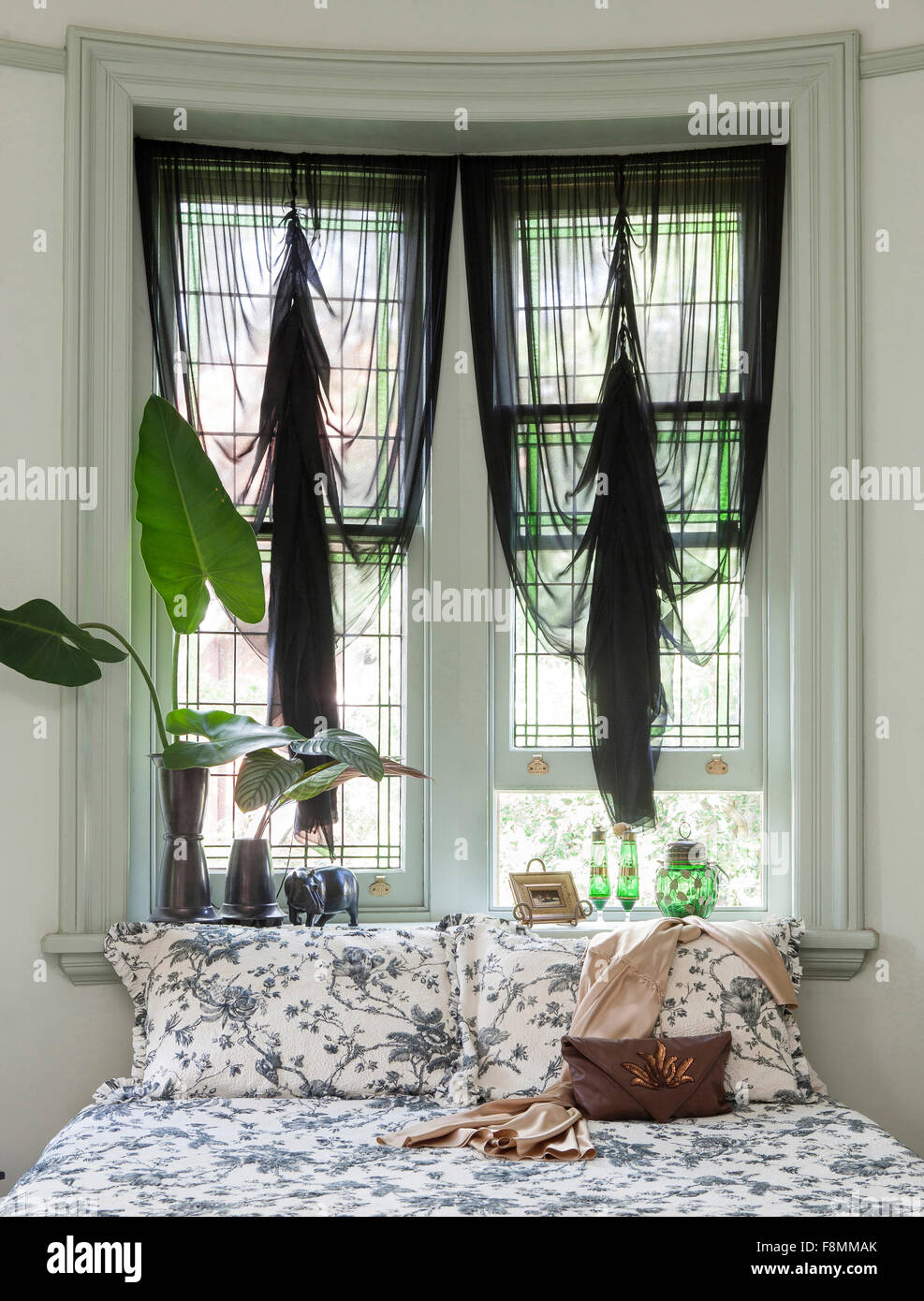 The home of designer Erica Pols. A bedroom. Windows drapped with ruched black net curtains. Floral bedlinen on a - Stock Image