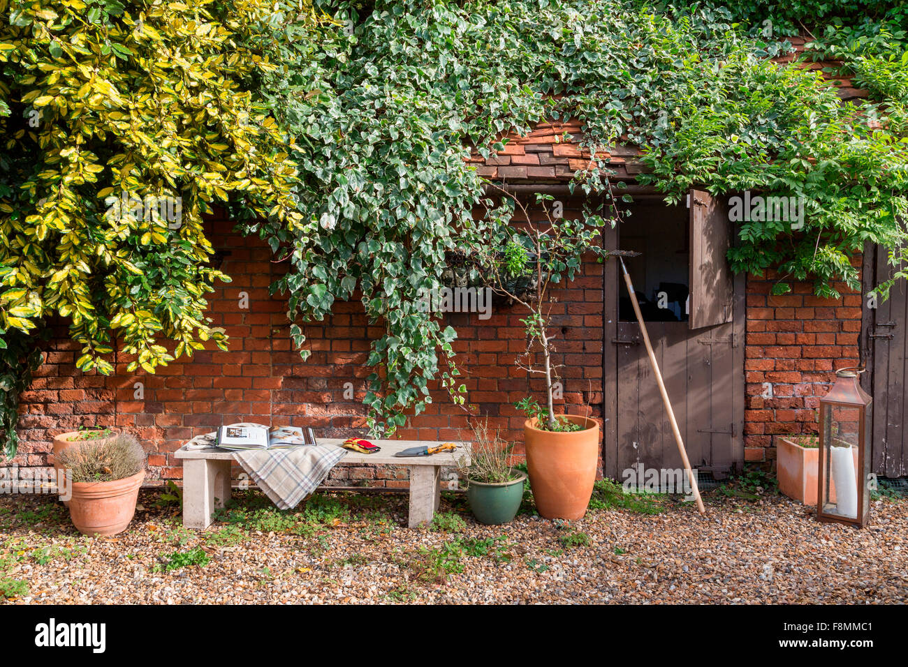 Grade II Listed Country Lodge in Weybridge. The old stable building at a historic house, with plant pots and a hurricane - Stock Image