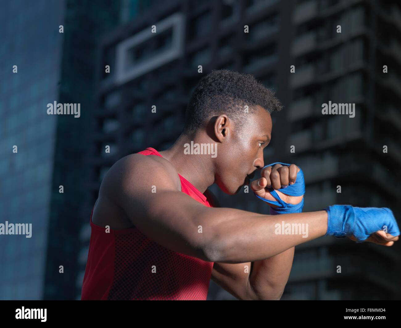 Portrait of boxer throwing punch, building in background Stock Photo