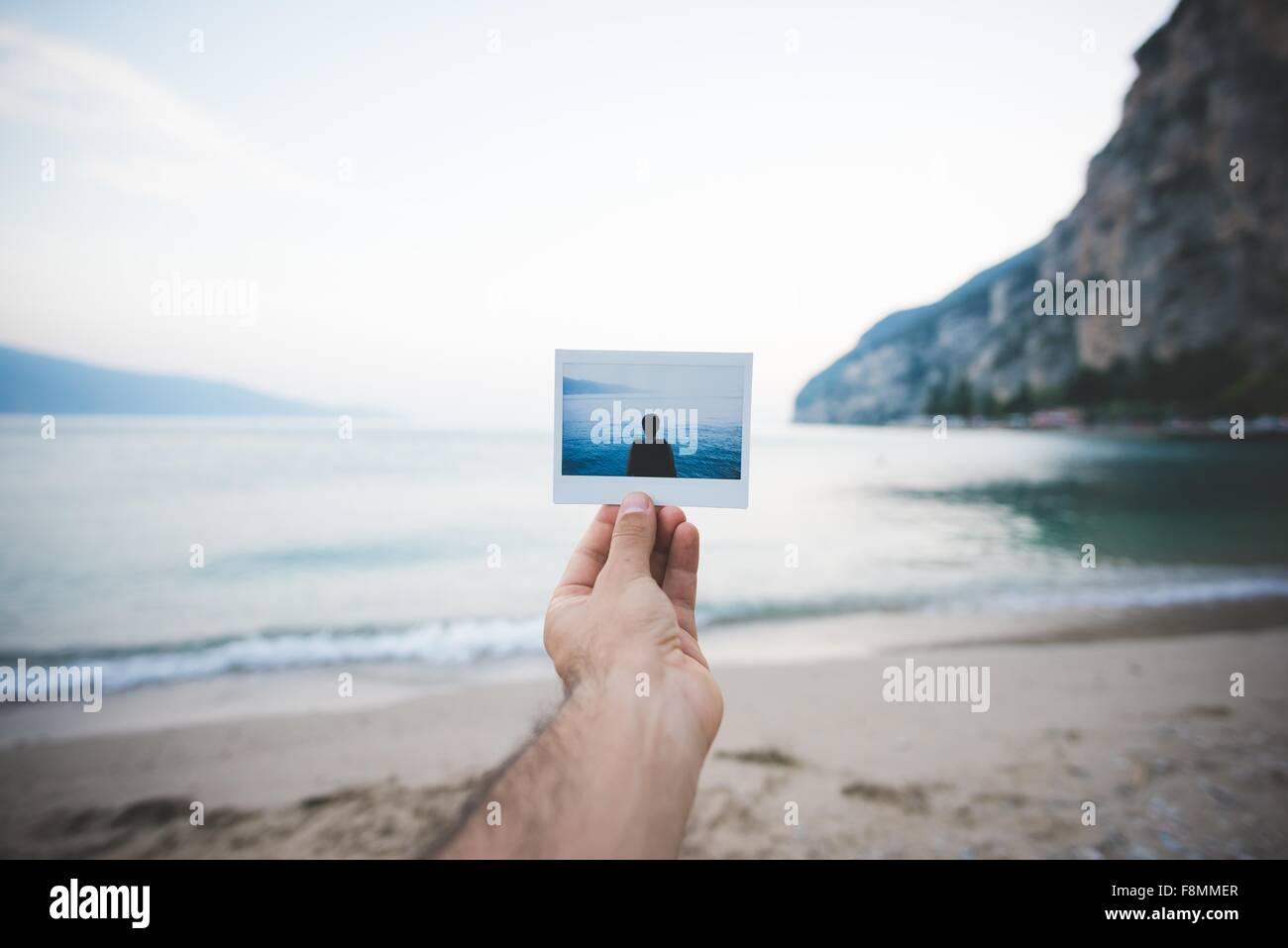 Person holding up photograph, Lake Garda, Italy - Stock Image