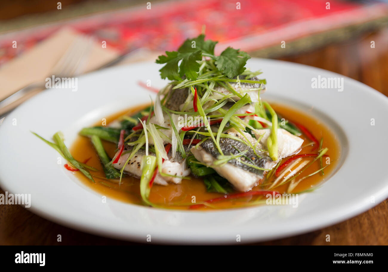 Singapore cuisine served in a restaurant. Fish. - Stock Image
