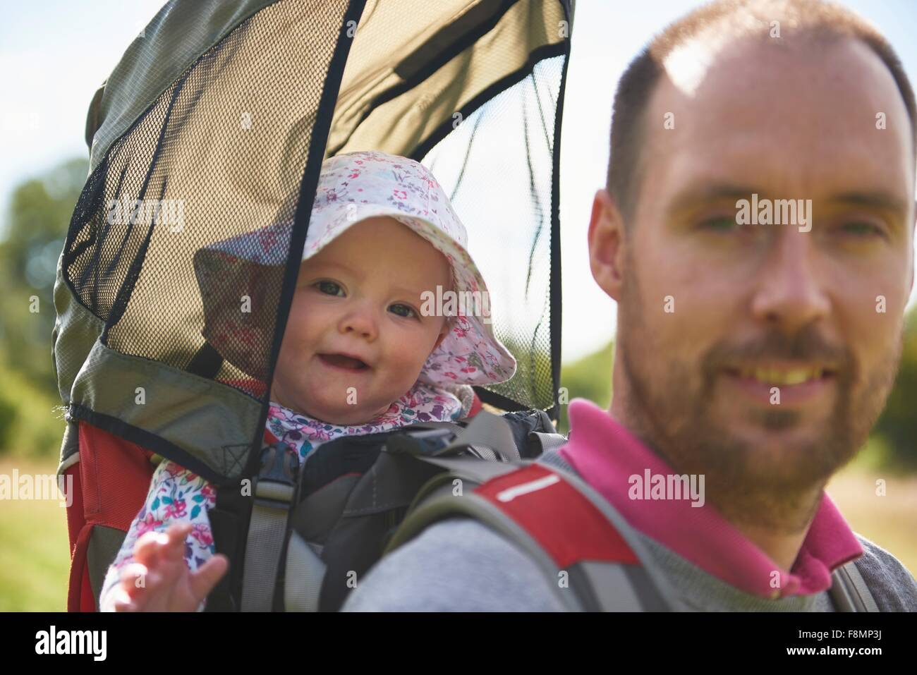 Father carrying baby daughter on back - Stock Image