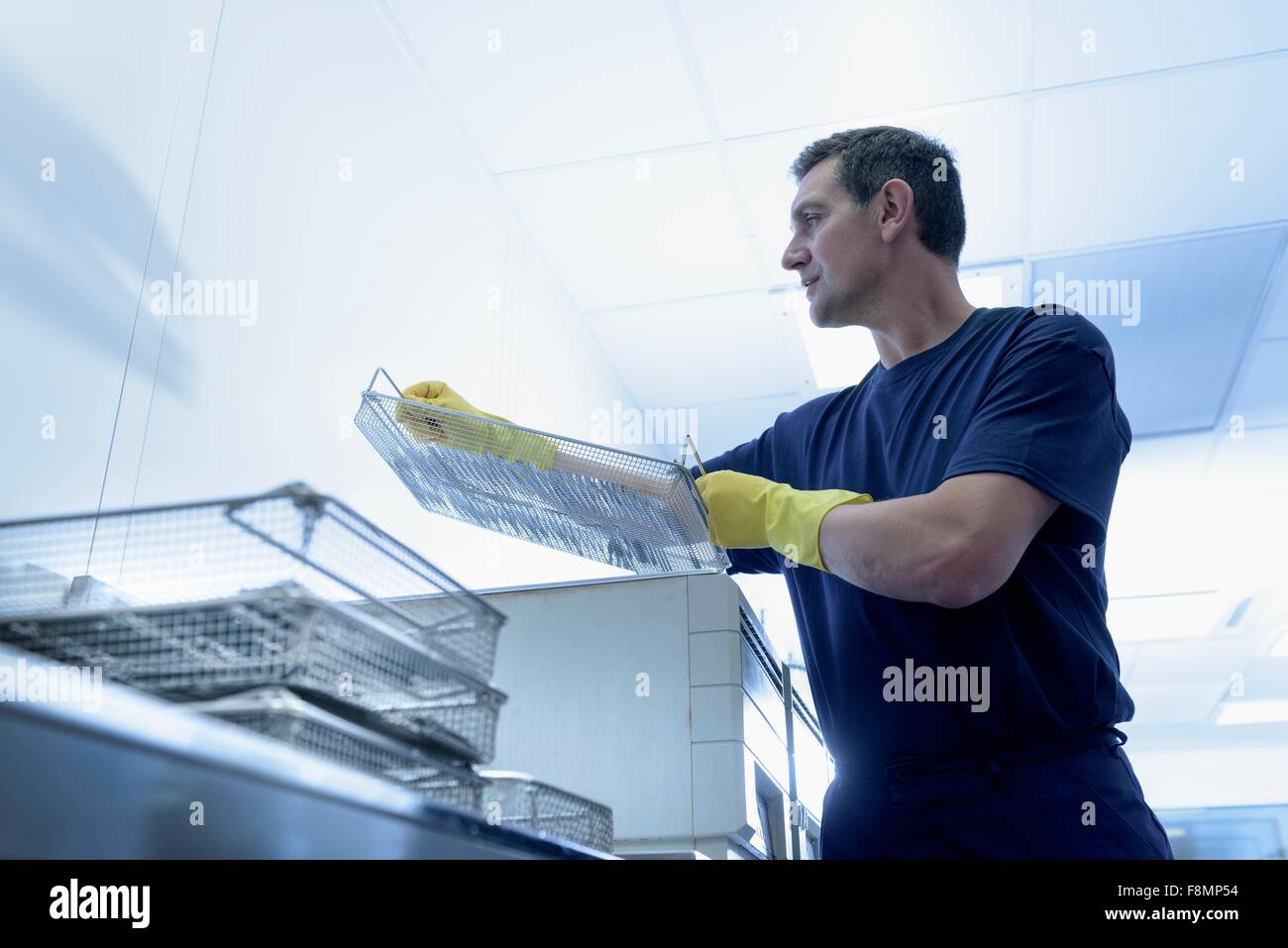 Worker putting surgical instruments into ultrasonic bath in surgical instrument factory - Stock Image