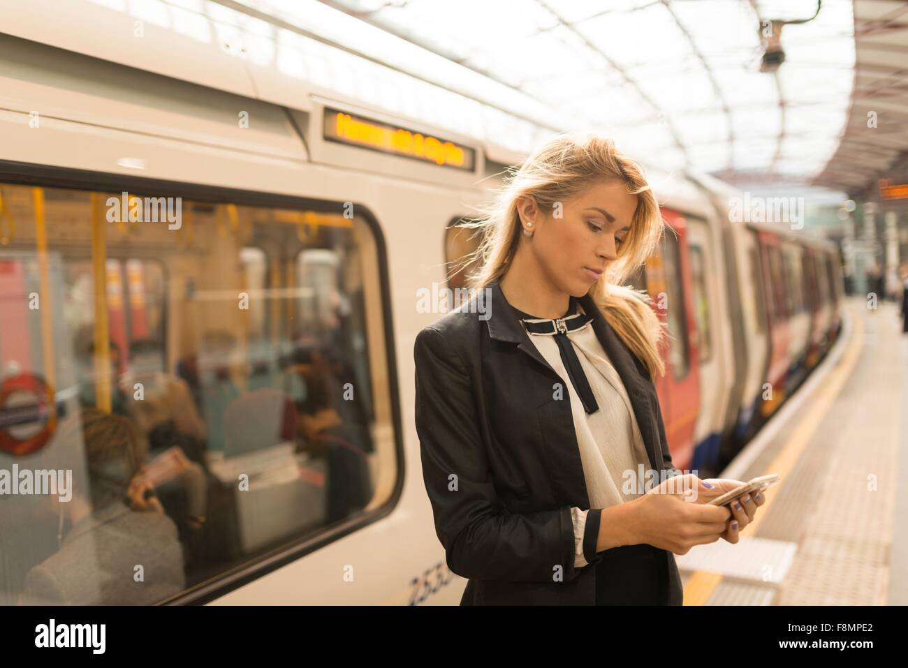 Business woman texting on platform, Underground station, London, UK - Stock Image