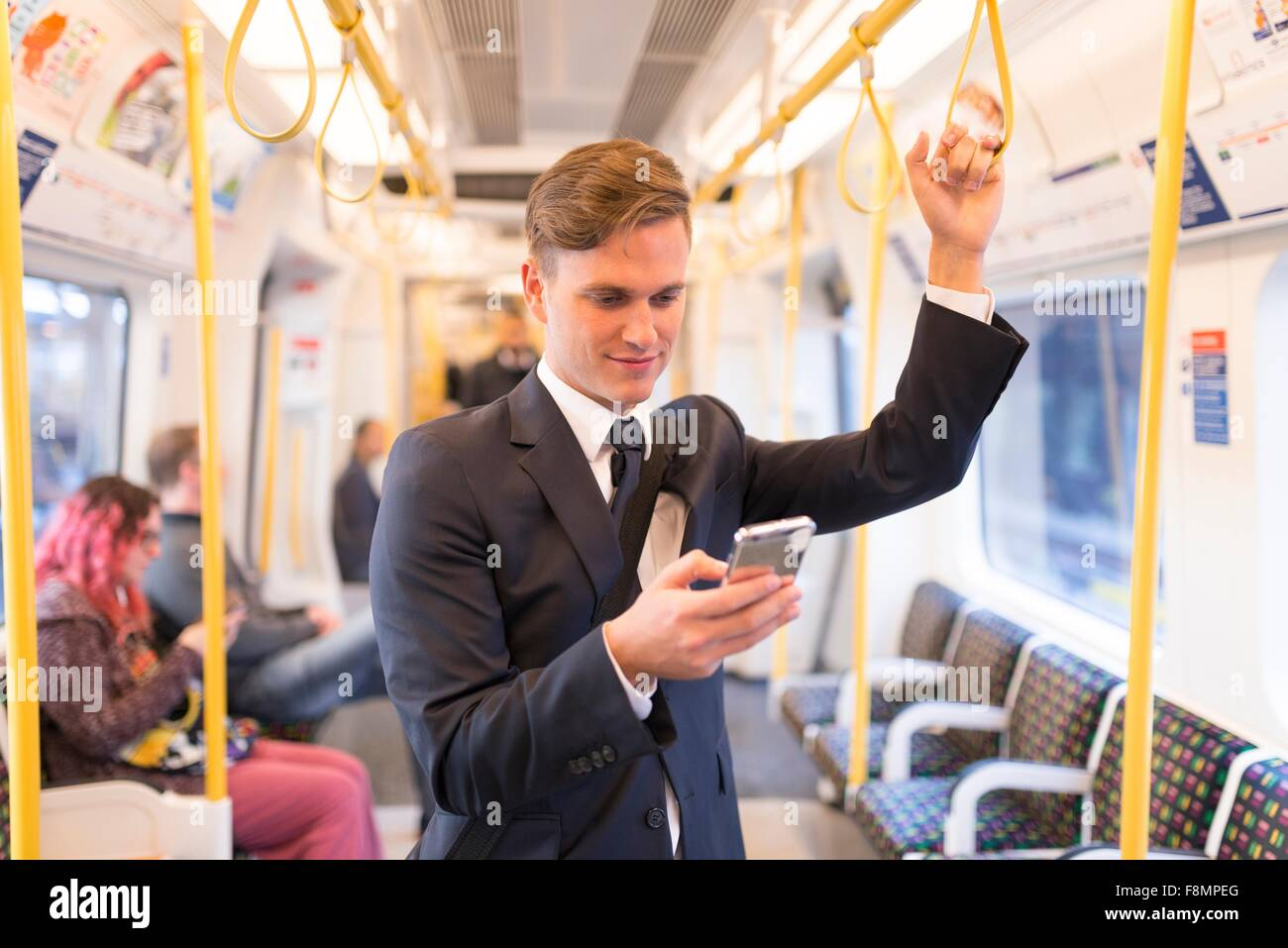 Businessman texting on tube, London Underground, UK - Stock Image