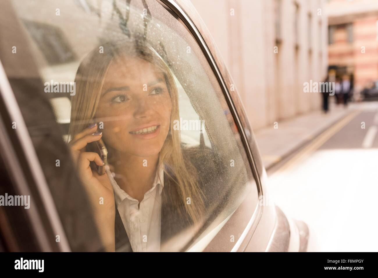 Businesswoman looking out of black cab, London, UK - Stock Image