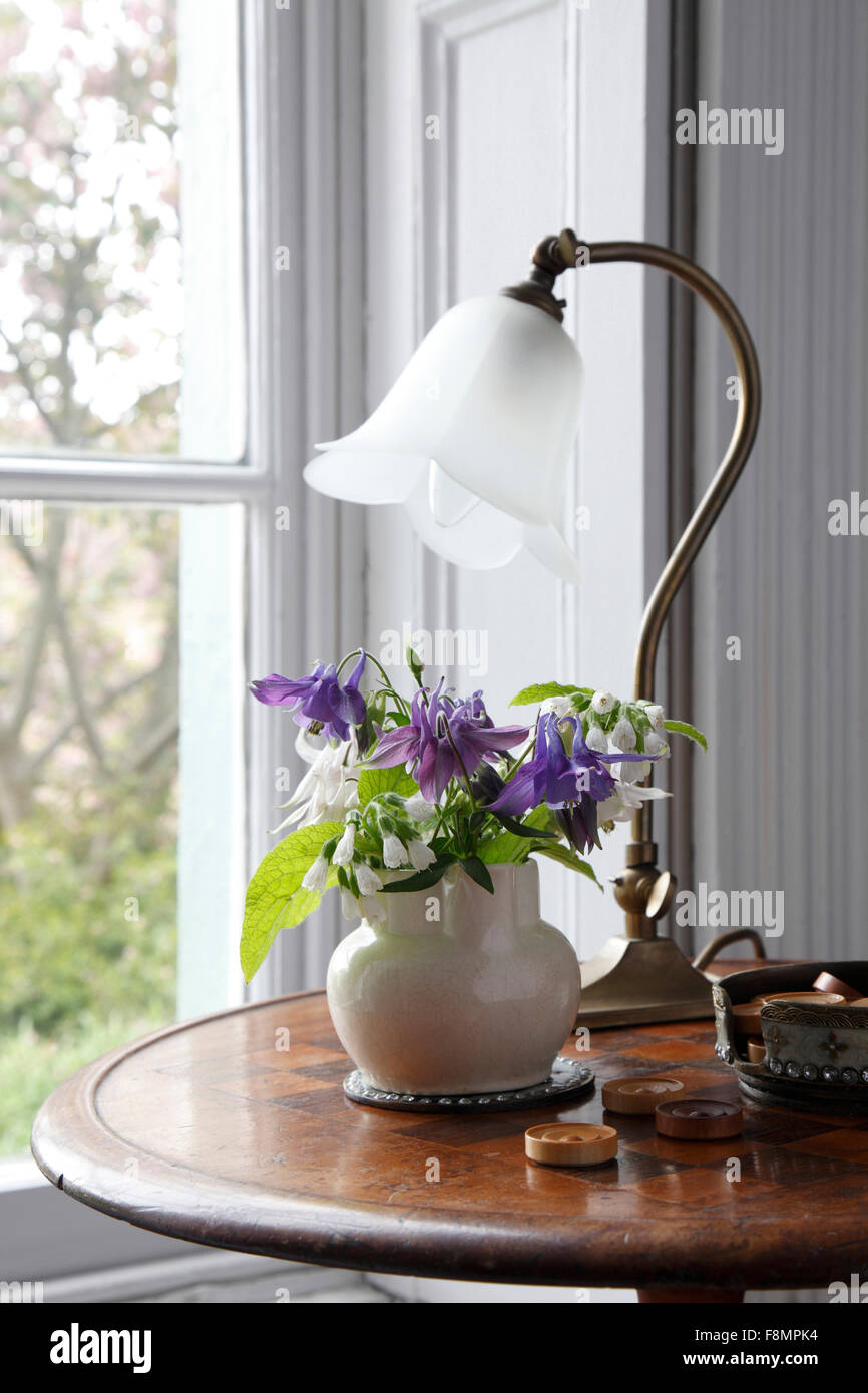 Draughts table in window with little vase of flowers and art nouveau brass lamp - Stock Image