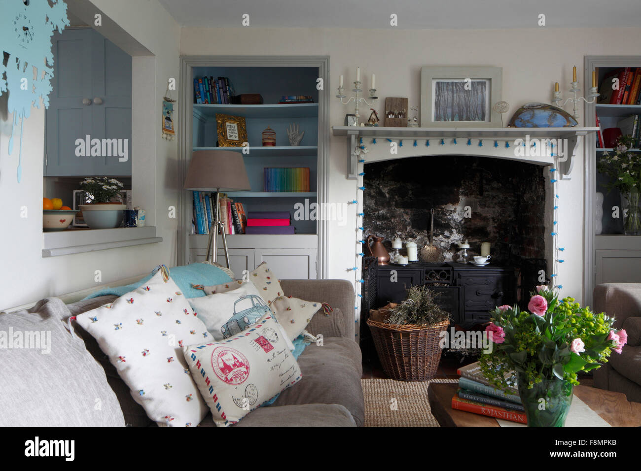 Wide shot of fireplace with recessed cupboard and shelves either side, and opening to kitchen - Stock Image