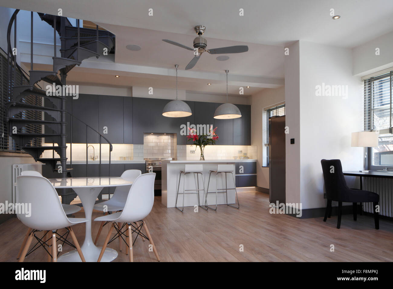 Wide Angle Of Living Space And Kitchen With Spiral Staircase. Lights On