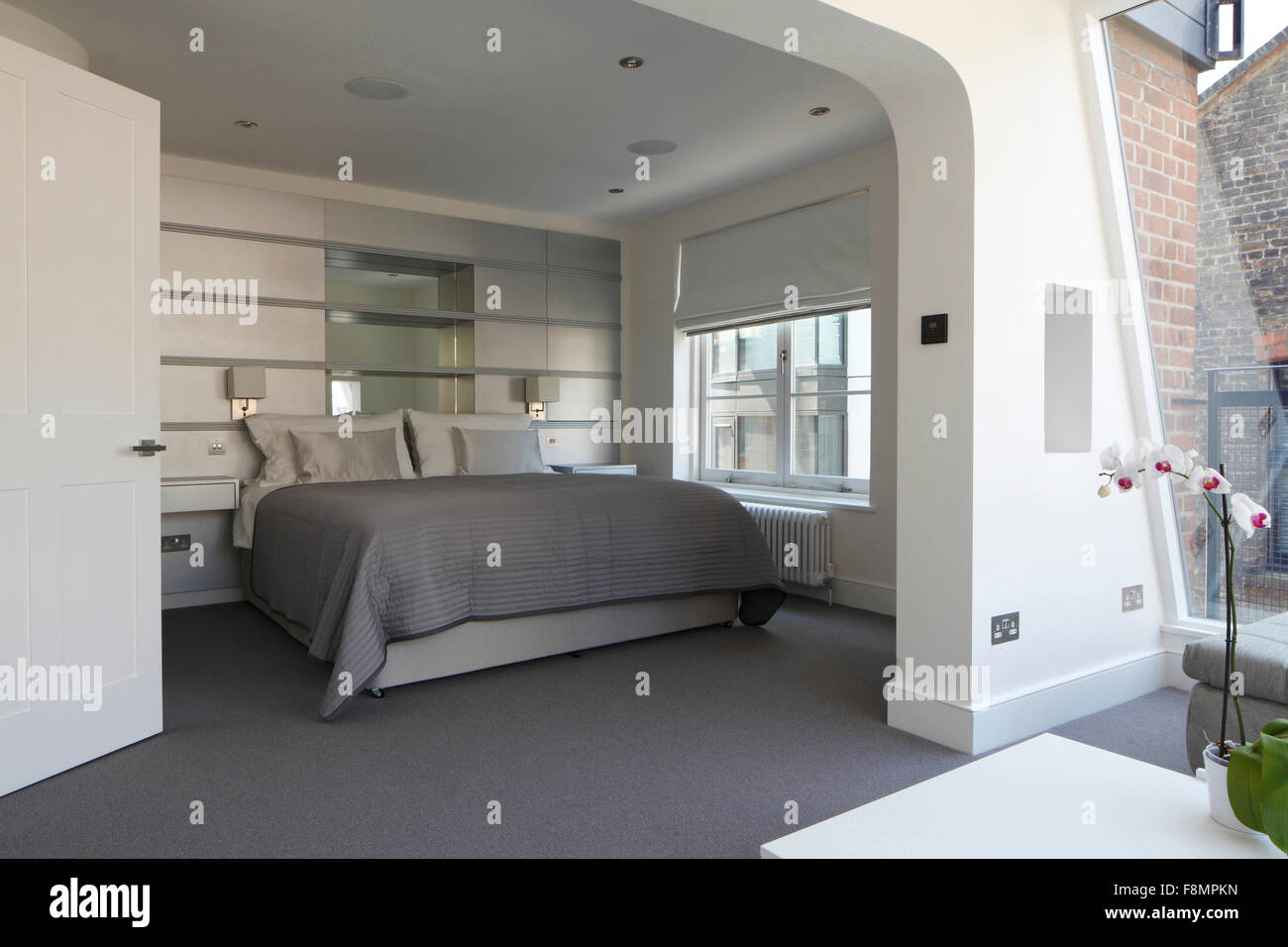 Wide shot of bedroom with silver grey colour scheme. Lights off - Stock Image