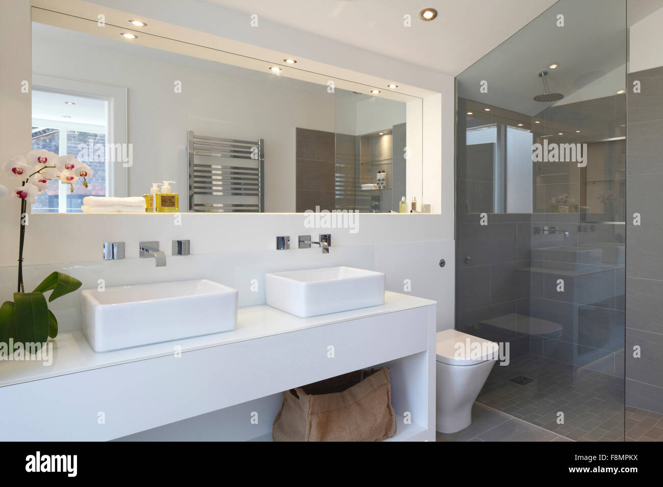 Bathroom with twin white basins over white vanity unit and grey tiled shower enclosure