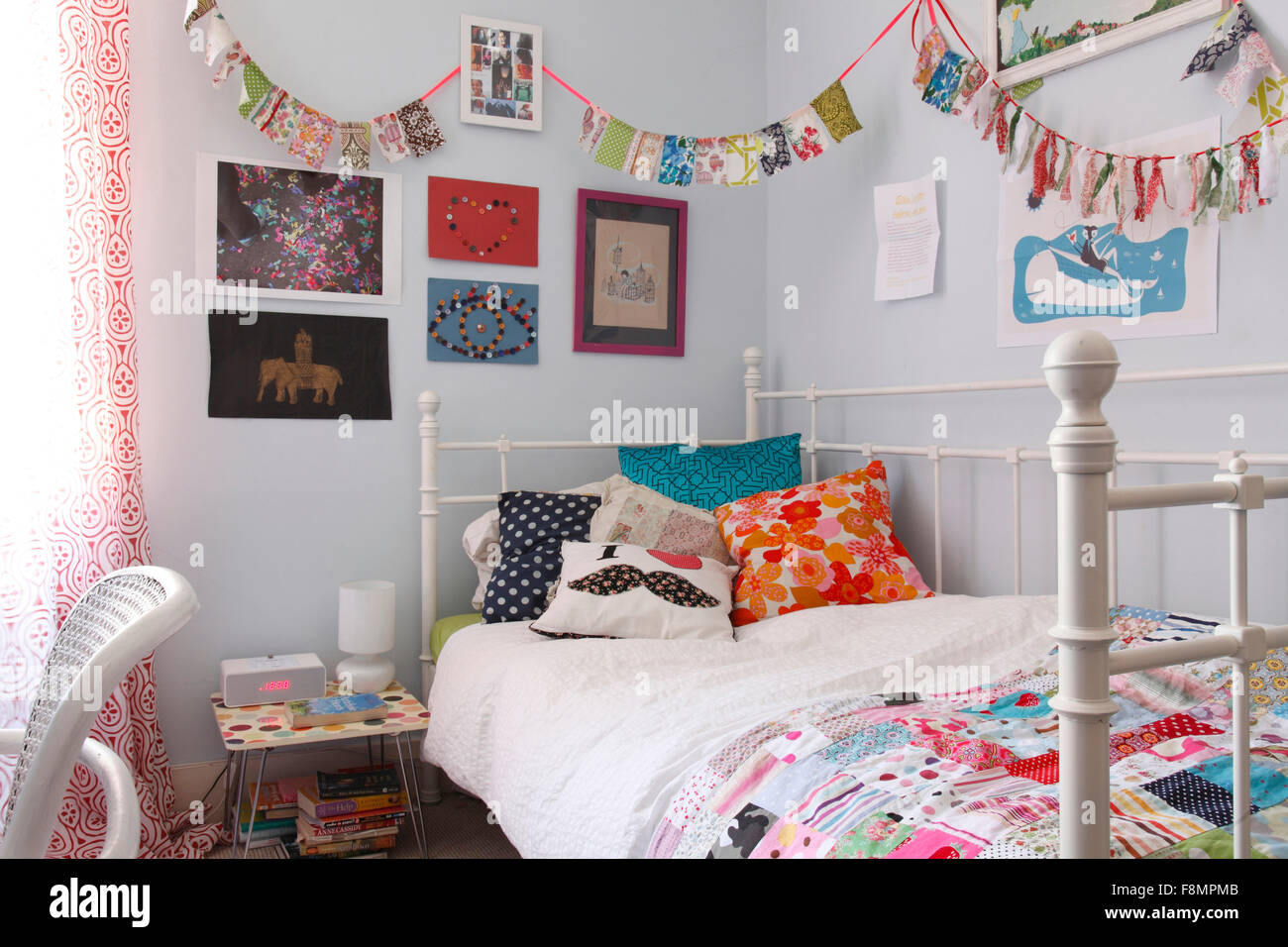 Little girl's bedroom with patchwork quilt and bunting - Stock Image
