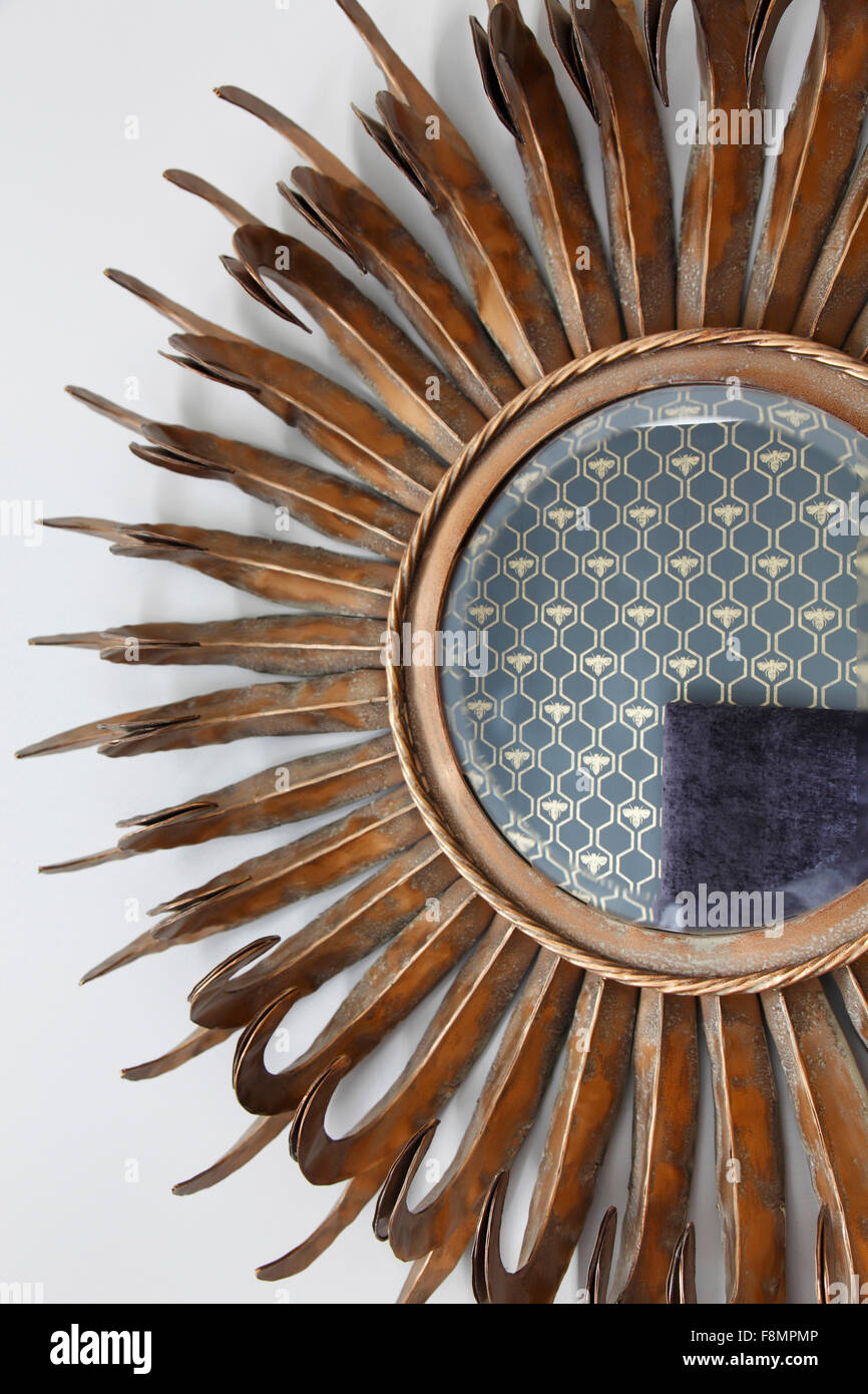 Sunburst mirror reflecting hexagonal pattern wallpaper with bee motif - Stock Image