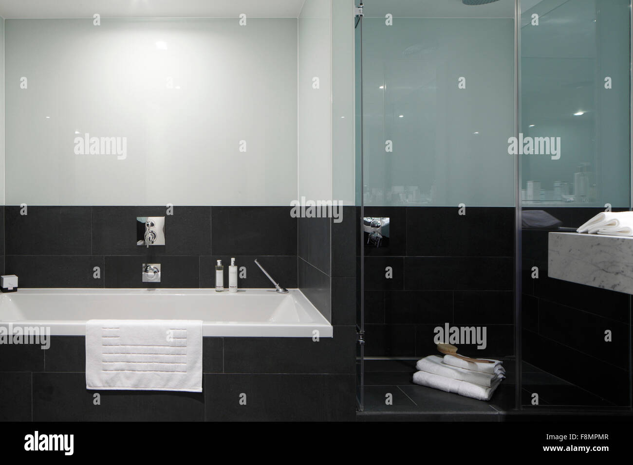 Bath and shower cubicle with charcoal grey tiling - Stock Image
