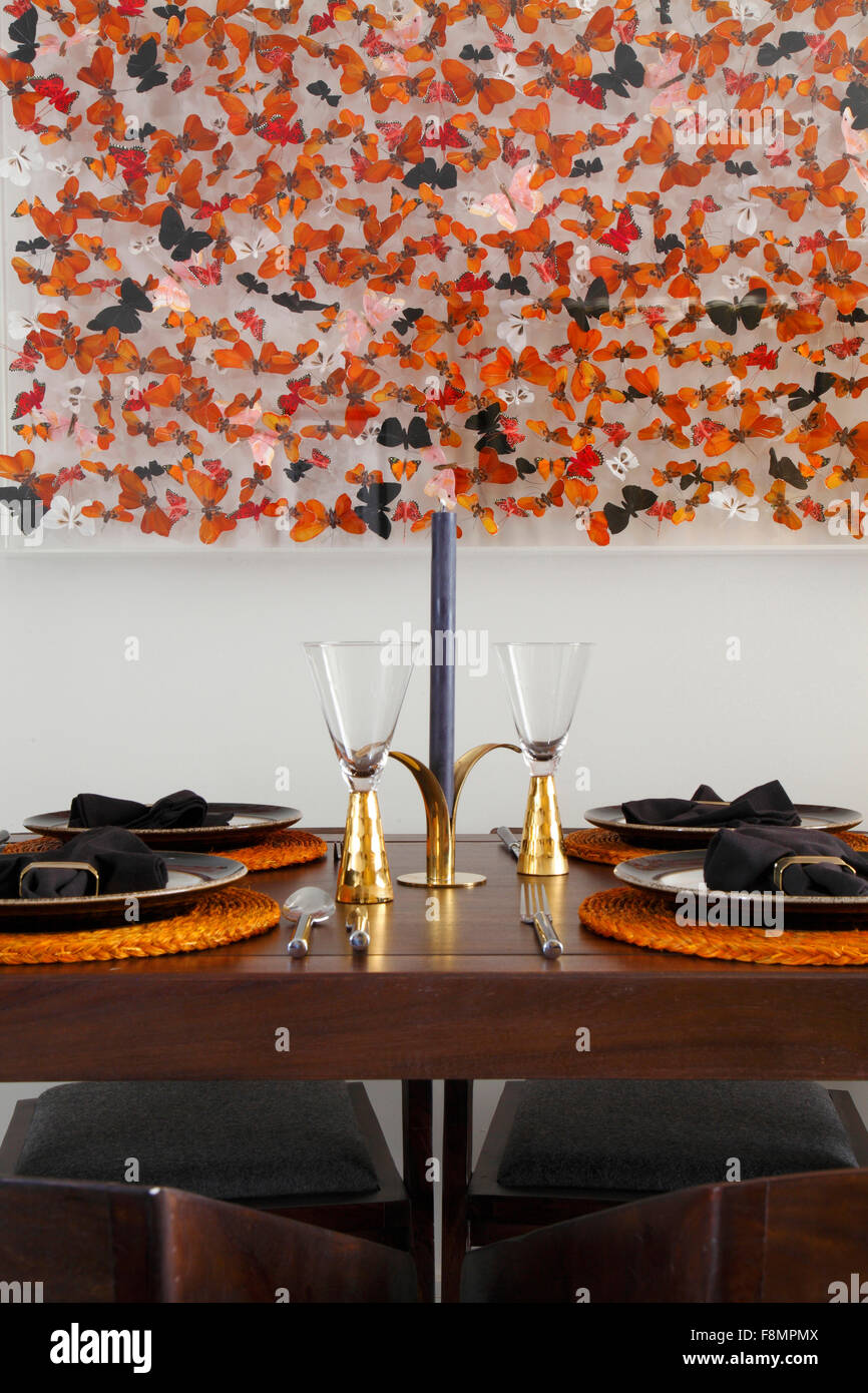 Place settings at dining table beneath butterfly art. - Stock Image