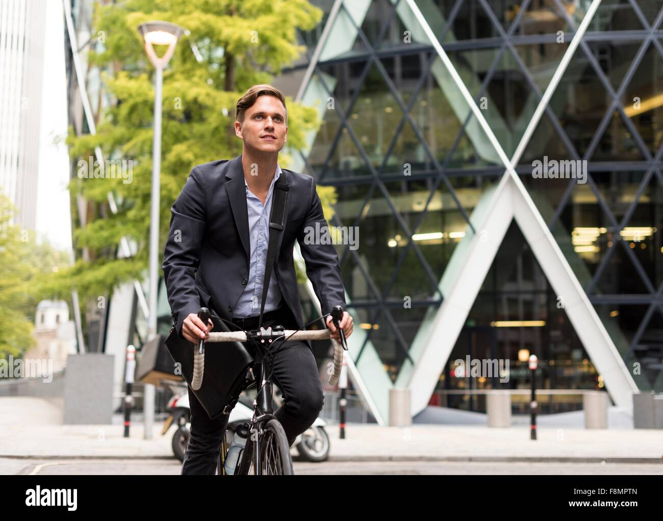 Businessman on bike, 30 St Mary Axe in background, London, UK - Stock Image
