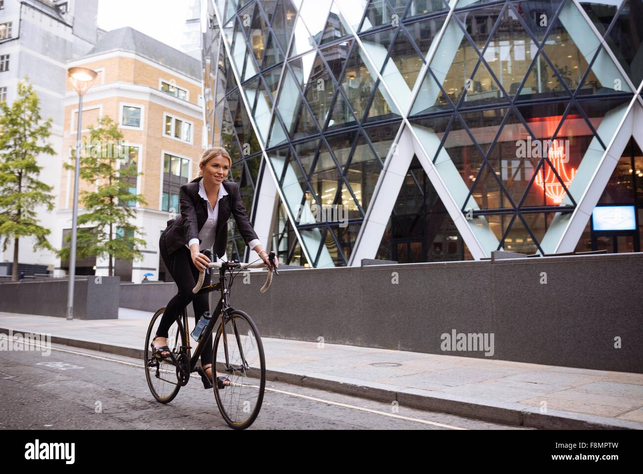 Businesswoman on bike passing 30 St Mary Axe, London, UK - Stock Image