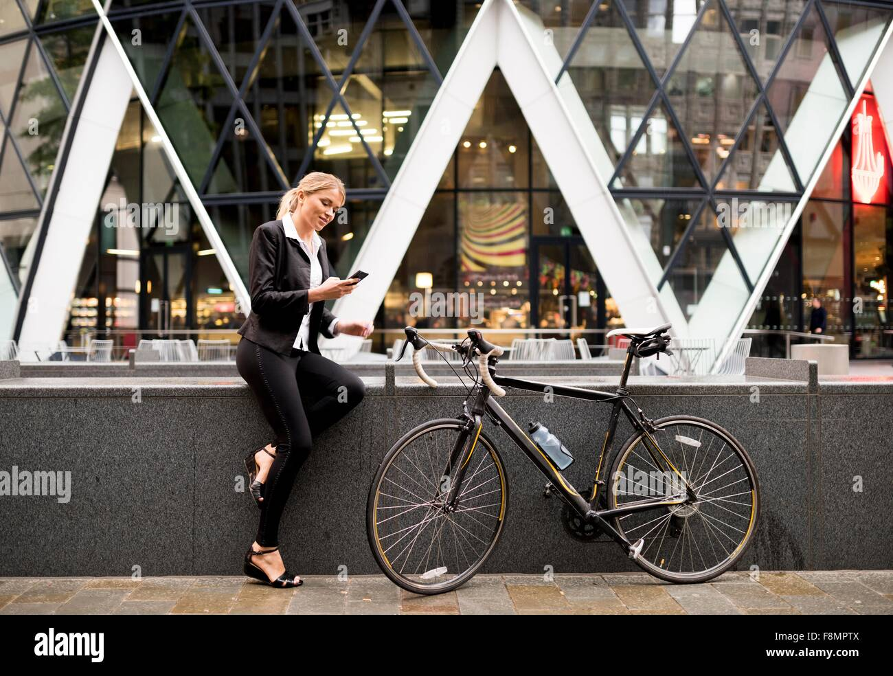 Businesswoman with bike outside 30 St Mary Axe, London, UK - Stock Image