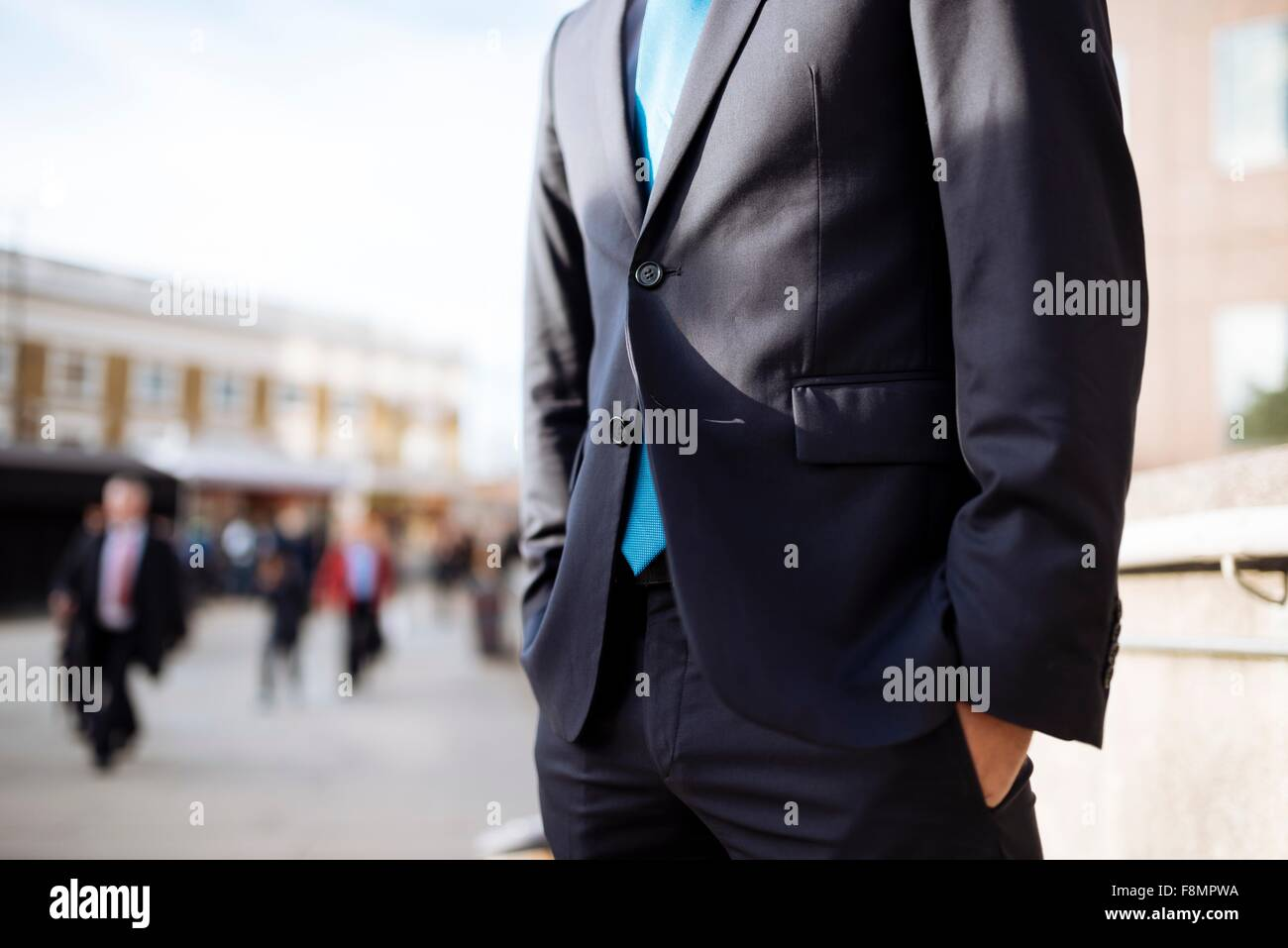 Businessman with hands in pocket, partially obscured, London, UK - Stock Image