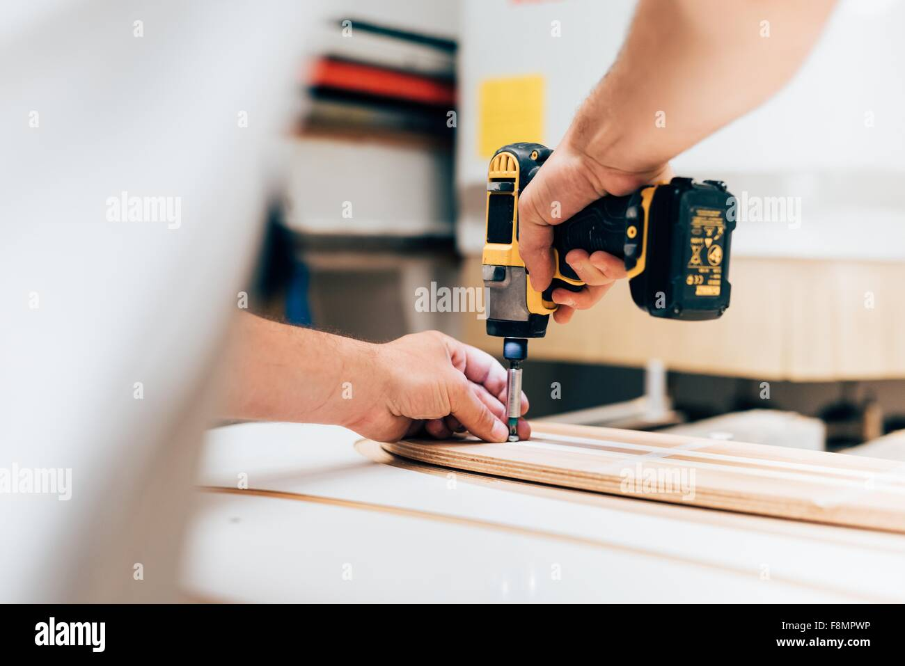 Cropped view of young man in carpentry workshop using cordless screwdriver, screwing into plywood - Stock Image