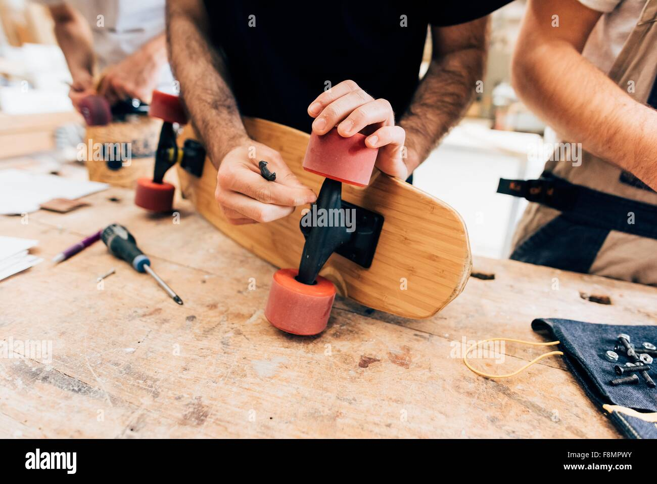 Cropped view of young men in workshop attaching wheels to skateboard - Stock Image