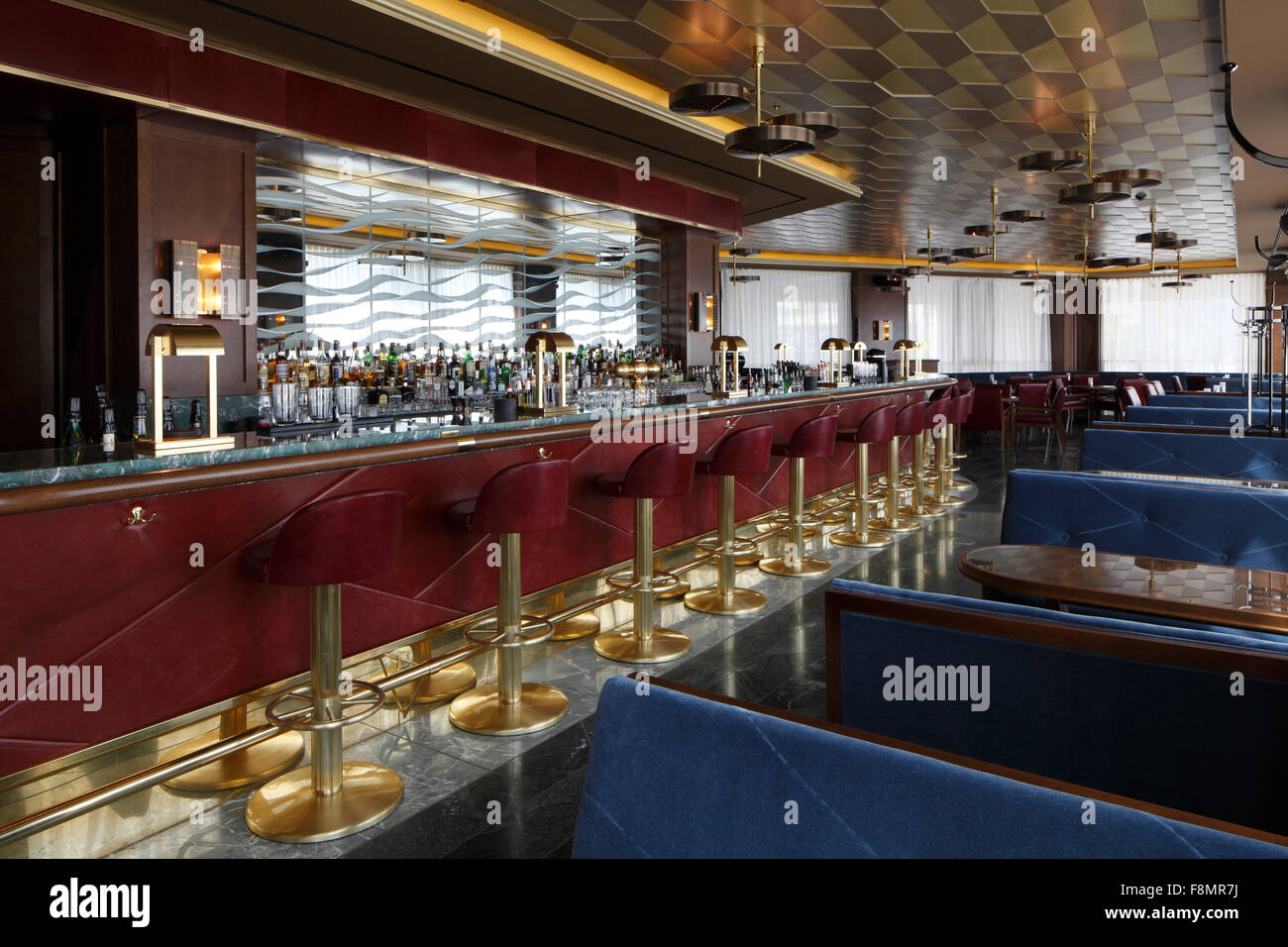 Red leather and brass barstools lined up perfectly along the bar