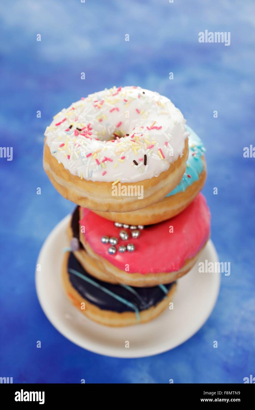 Four doughnuts with colourful glaze and sugar sprinkles - Stock Image