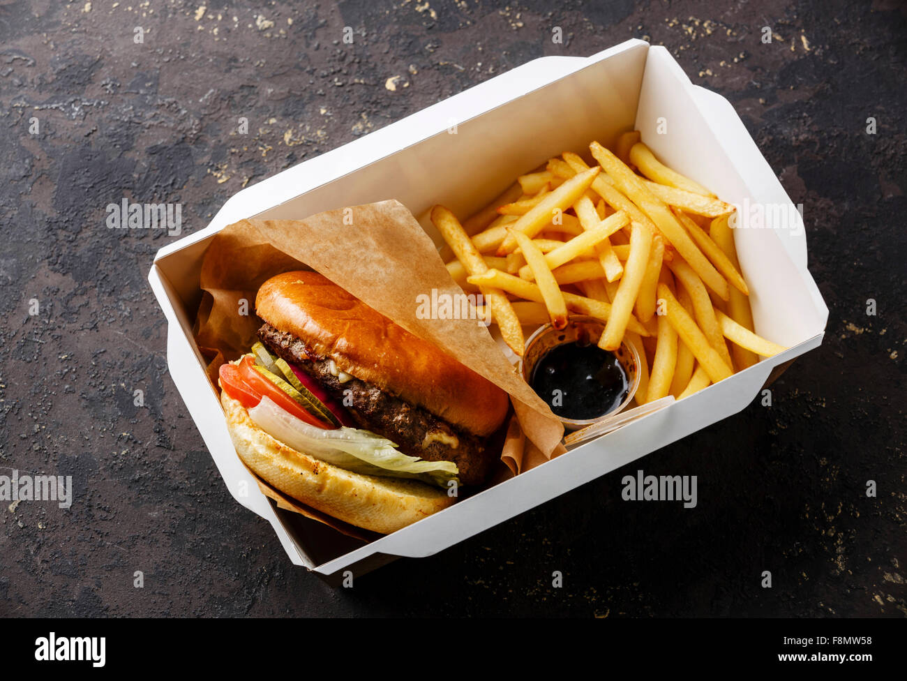 Burger with meat and French fries in paper box on dark background - Stock Image