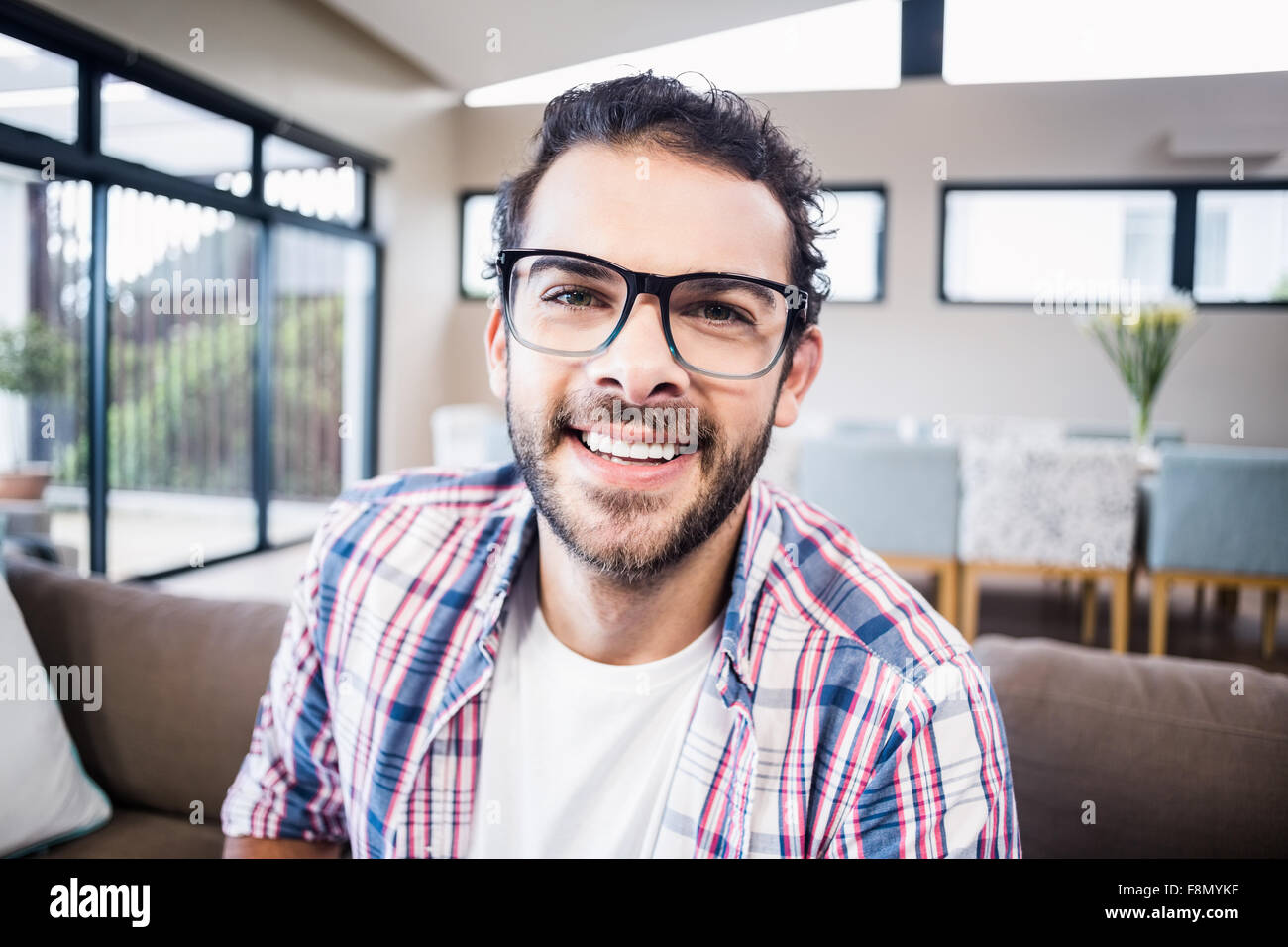 Handsome man smiling at the camera - Stock Image