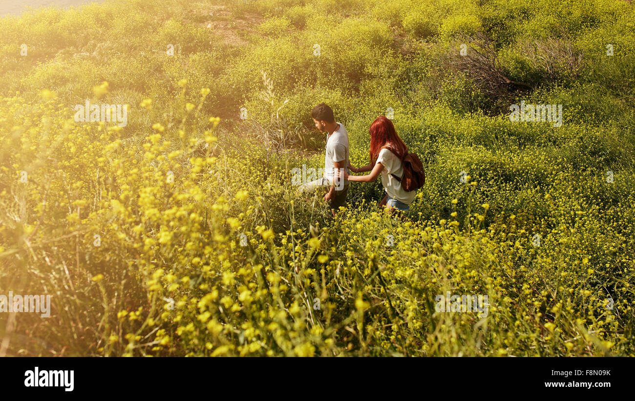 Shot of young couple walking through grass on a peak. Young man and woman hiking on a summer day. - Stock Image