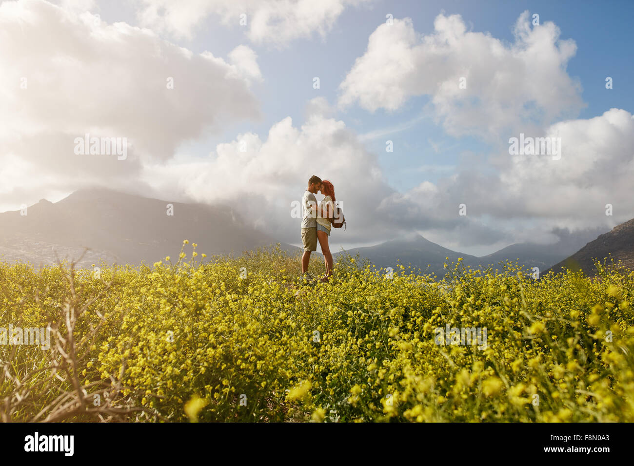 Romantic young couple embracing and  looking at each other, while standing on a hill top outdoors on a summer day. - Stock Image