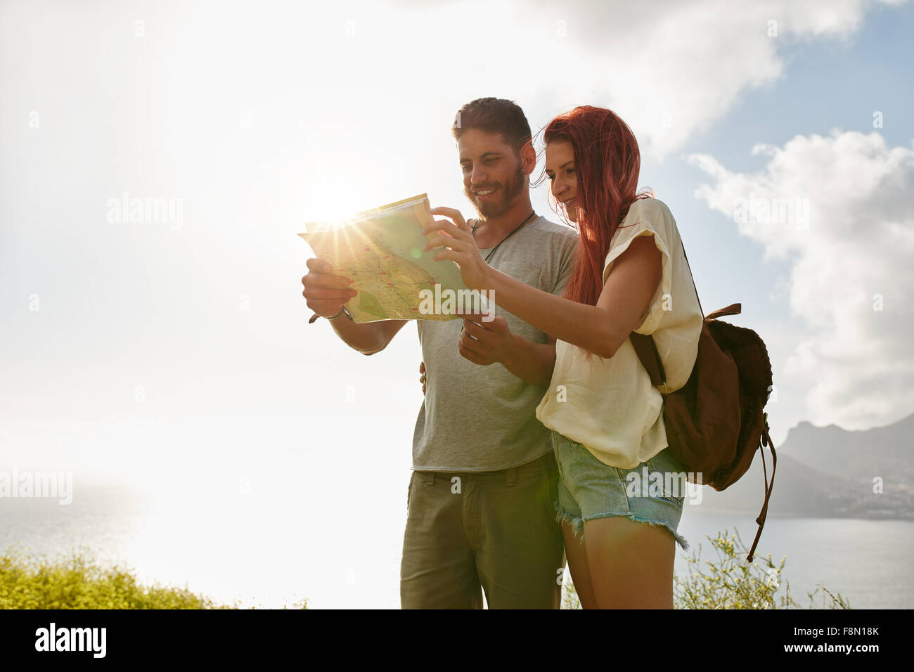 Man and woman looking for directions on map. Couple stopping to check their map while walking in countryside. - Stock Image