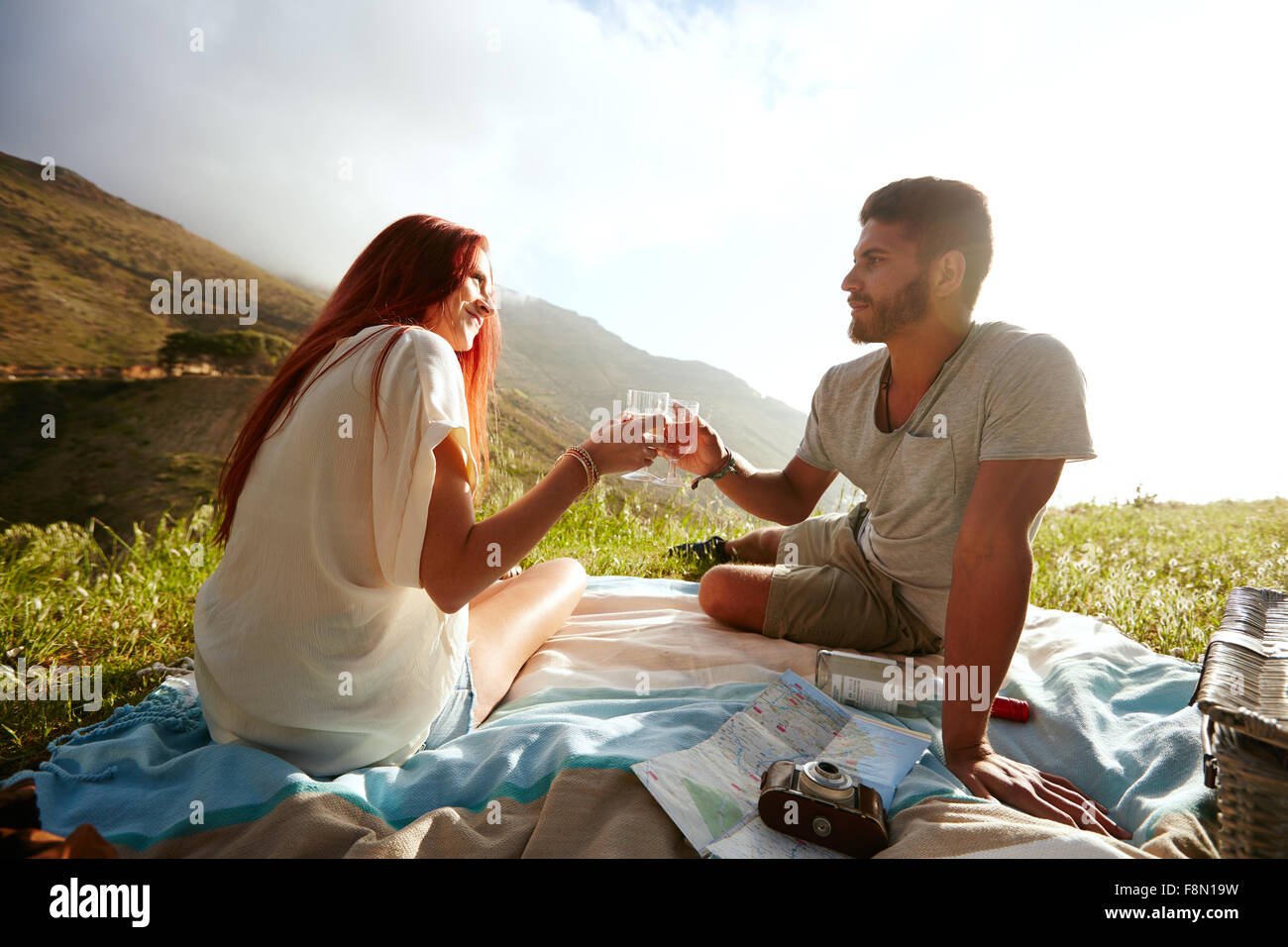 Love couple sitting on the grass and drinking wine during a picnic. Caucasian man and woman on summer holiday. Couple - Stock Image