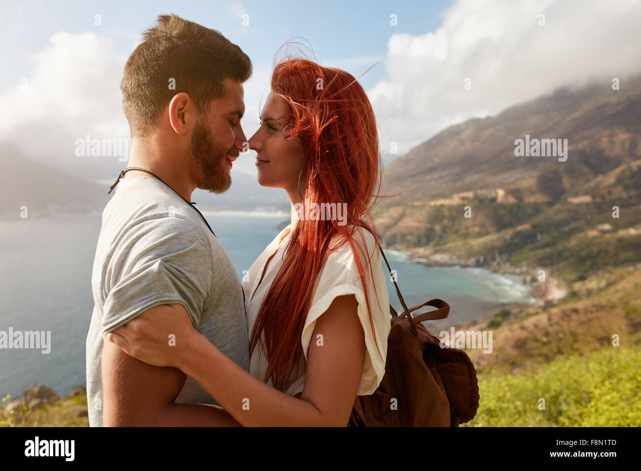 Portrait of young man and woman standing face to face. Affectionate young couple enjoying their love in nature outdoors. - Stock Image