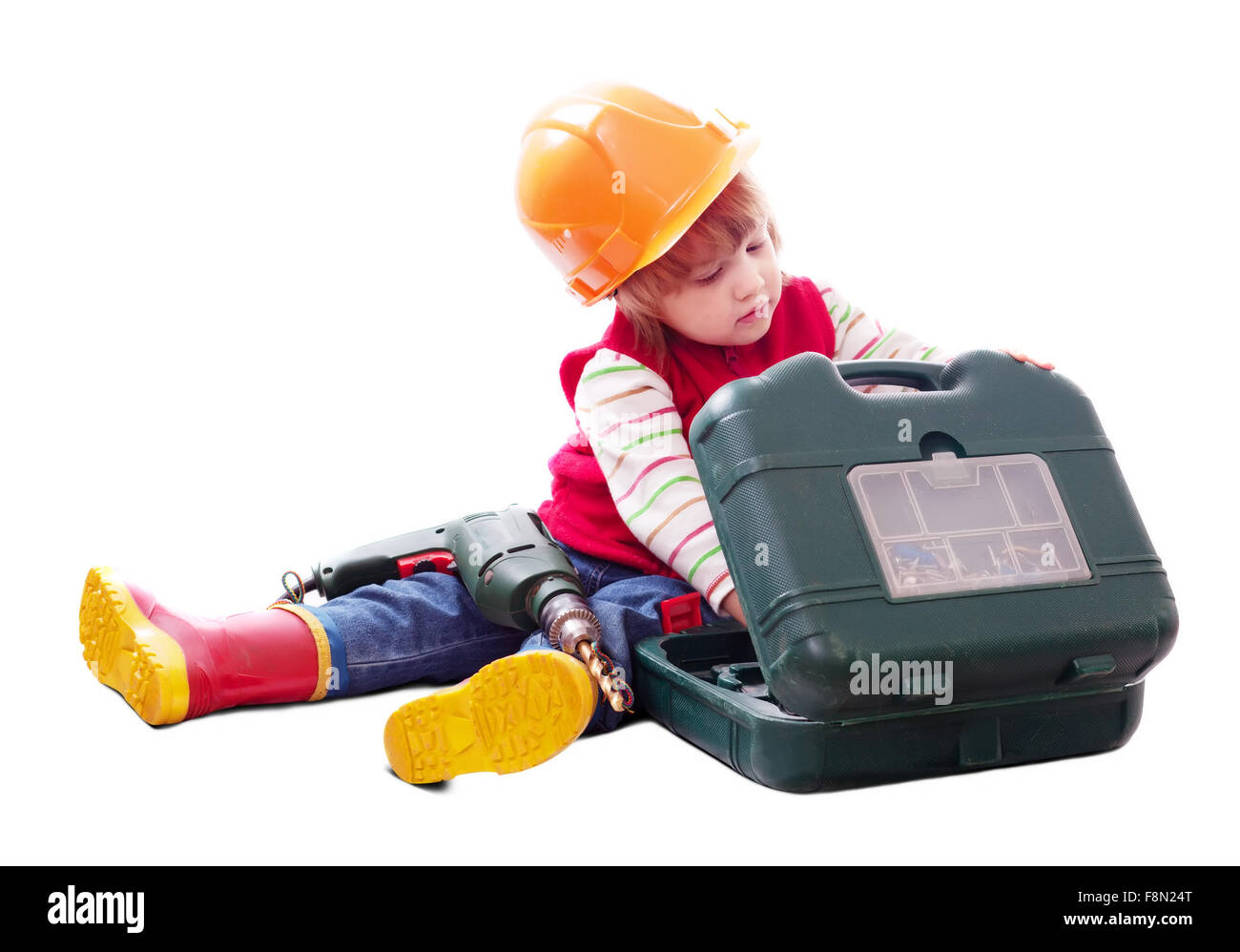 2 years child in hardhat chooses tools in toolbox. Isolated over white background  with shade - Stock Image