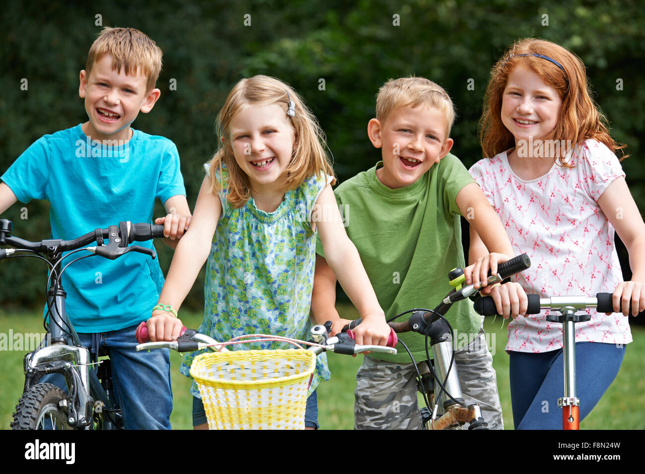 Group Of Children Playing On Bikes And Scooter - Stock Image