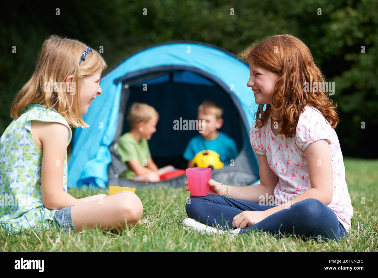 Two Girls Chatting Together On Camping Trip - Stock Image