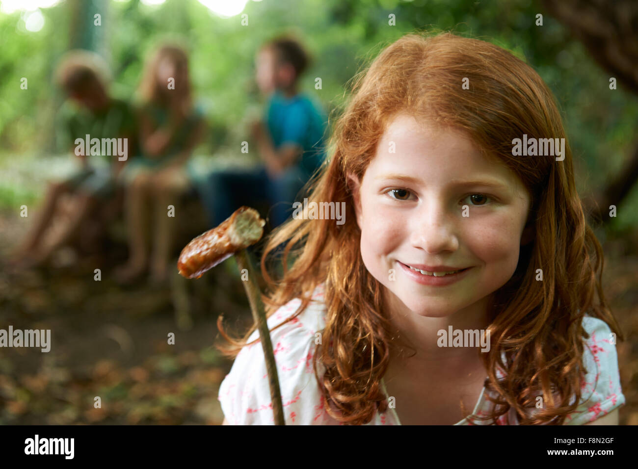 Girl Eating Sausage Cooked On Camp Fire With Friends - Stock Image
