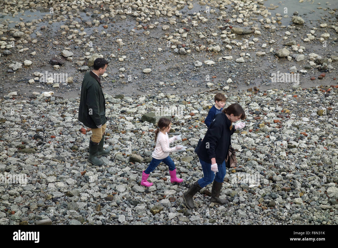 Family of mudlarks on foreshore of River Thames, London Stock Photo