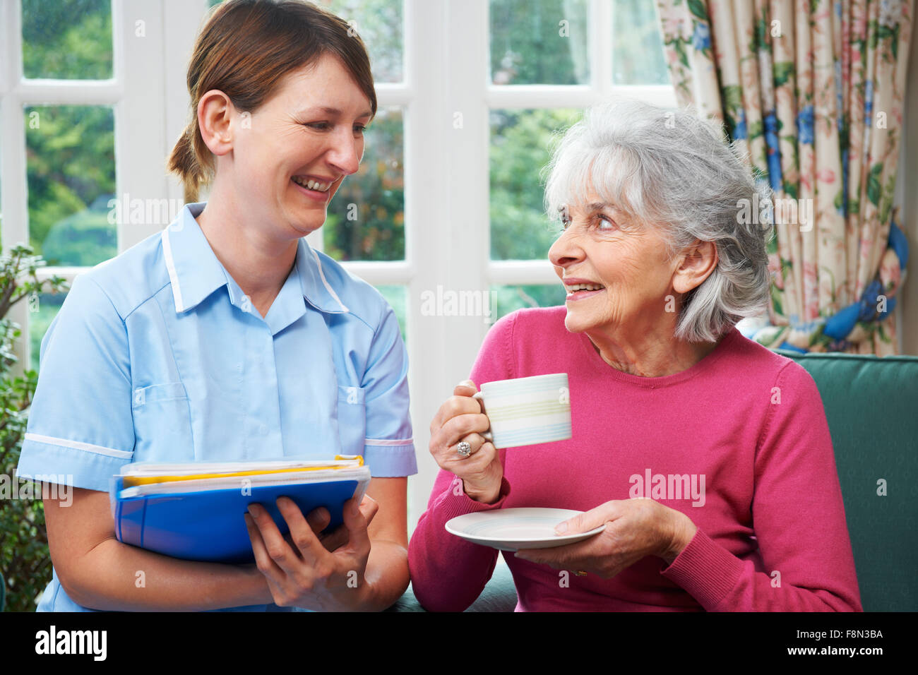 Senior Woman Being Visited By Carer At Home - Stock Image