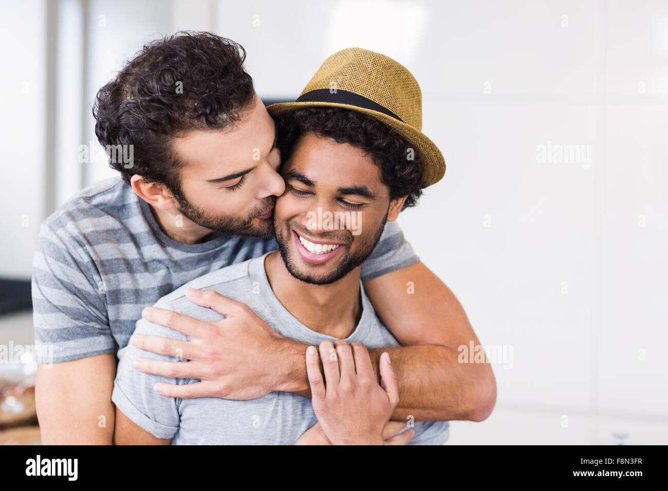 Handsome man hugging and kissing his boyfriends cheek - Stock Image